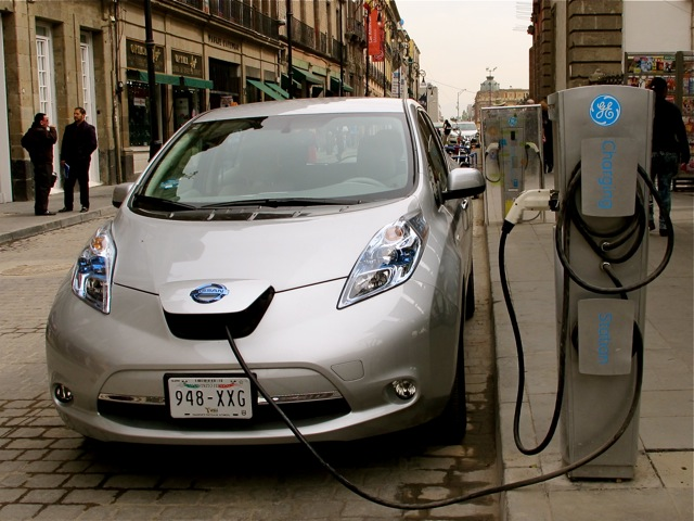 Silver Nissan electric car getting charged at charging station in the street.