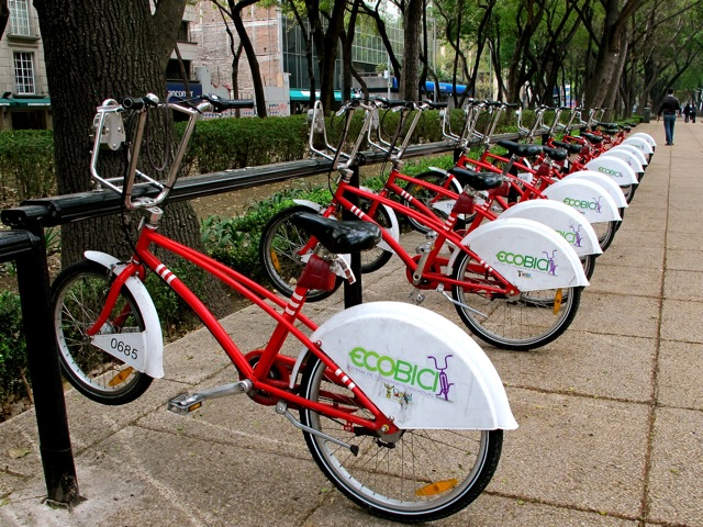 Red Ecobici bicycles lined up on bike rack.