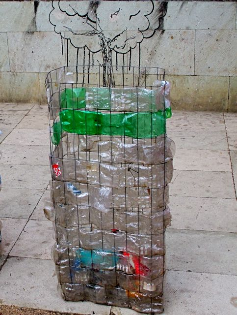 Plastic bottle recycling bin with graffiti drawing of a tree crying in the background.
