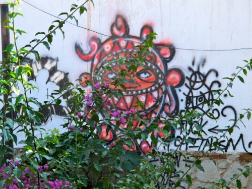 Multicolored creature painted on wall in back; with bougainvillea in foreground