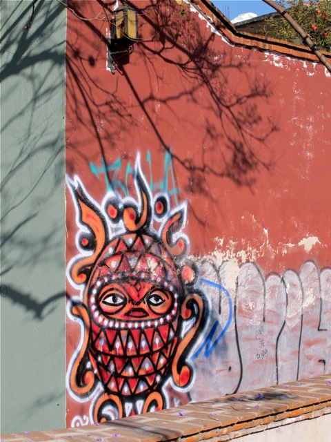 Multicolored creature painted on terracotta wall