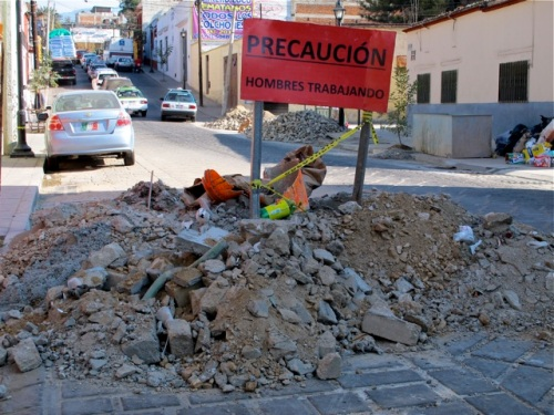 Pile of torn up street rubble in street, with red sign:  Precaución - Hombres Trabajando