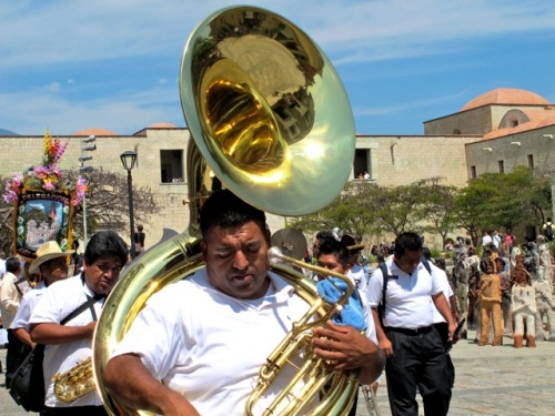 Man carrying a shiny brass tuba