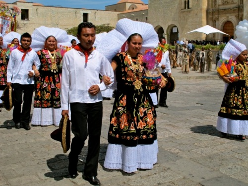Women in embroidered black velvet costumes and wearing white lace head pieces arm in arm with men in black pants, white shirts, red neck kerchief and carrying a sombrero