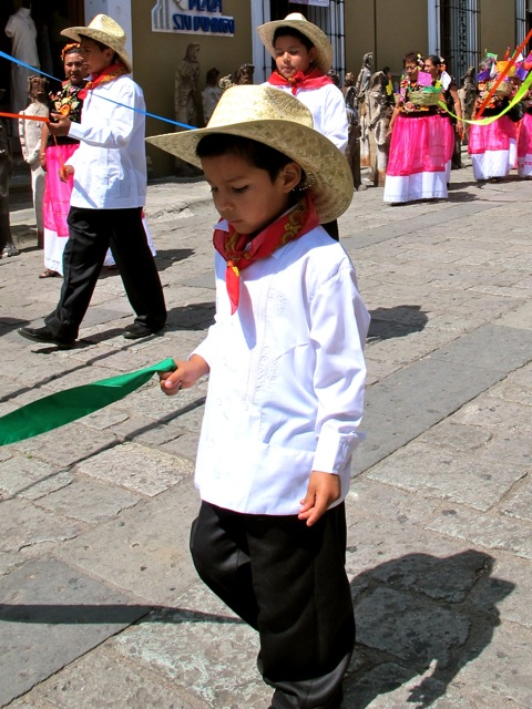 Little boy wearing black pants, white shirt, red neck kerchief, and sombrero