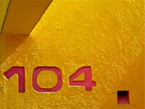 Magenta numbers 104 against bright yellow wall
