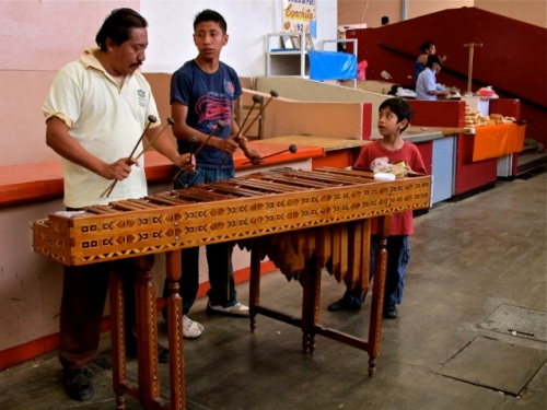 Man, teenage boy, and young boy playing marimba