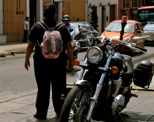 Female traffic officer with pink backback standing next to motorcycle