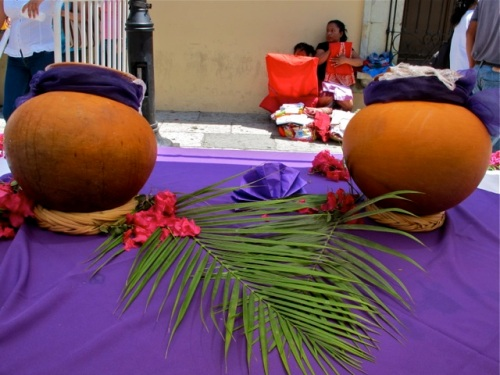 Clay pots and palm fronds on top of purple tablecloth