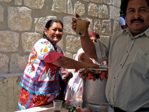 Woman in indigenous dress serving an agua, man in foreground holding cup