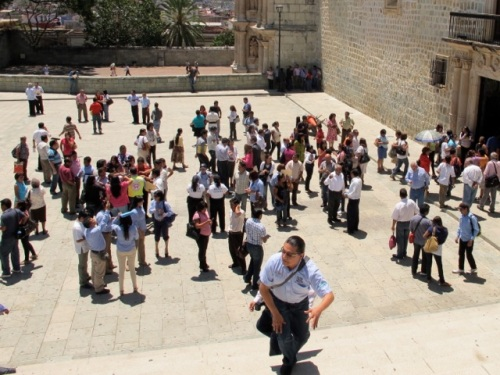 People standing around in the Plaza de la Danza in front of the Palacio Municipal