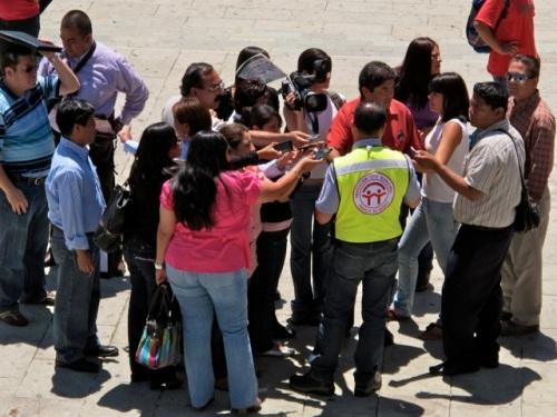 Representative of the Proteccíon Civil Municipal de Oaxaca in a yellow vest giving a press conference.