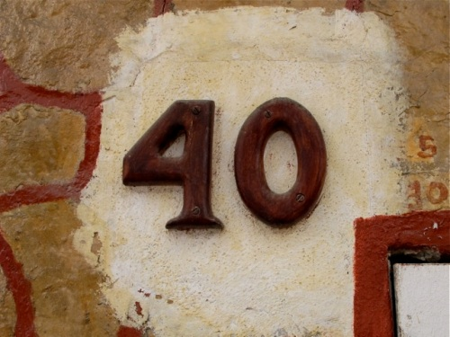 Wooden number 40 against white patch on tan rock wall with terracotta geometric design