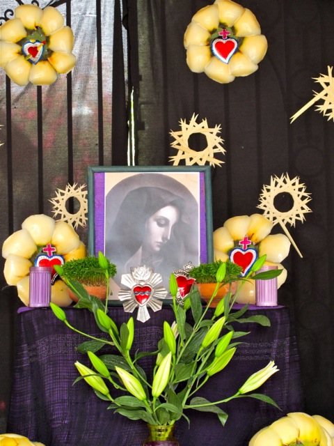 "Photo on altar of La Virgen de Dolores with vase of lilies in forground and palm ""flowers"" in background"