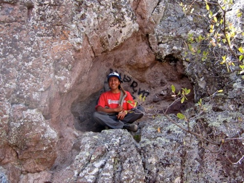 Sam sitting cross-legged in a natural alcove in the mountain