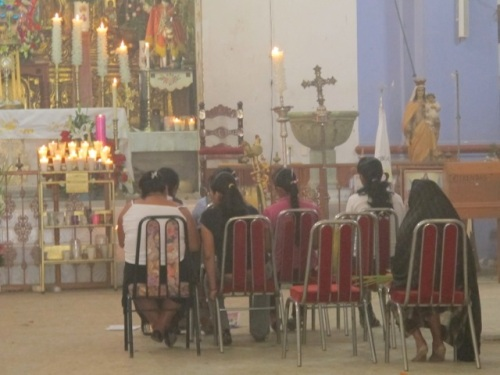 7 women sitting in chairs in front of an altar, in the haze of incense.