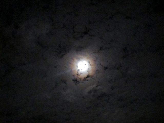 Full moon with halo shining from behind clouds