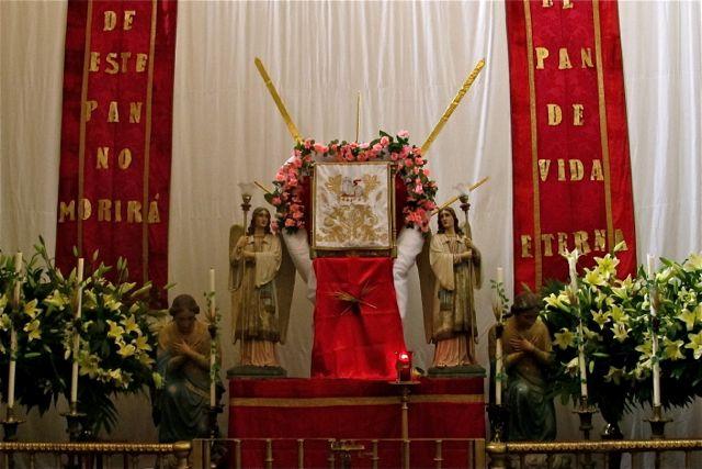 """Altar with red banners reading, """"De este pan no morirá; El pan de vida eterna"""""""