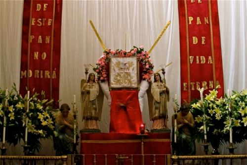 "Altar with red banners reading, ""De este pan no morirá; El pan de vida eterna"""