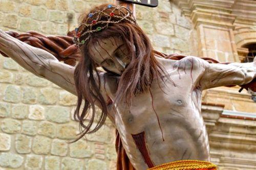 Close up of a bleeding Jesus head and torso on a cross