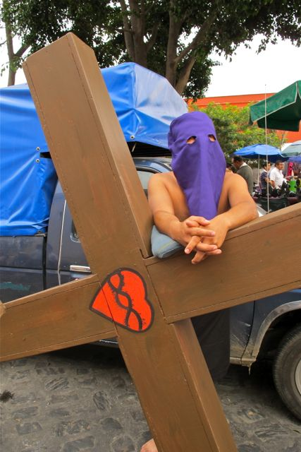 Man in purple hood, leaning against large wooden cross.