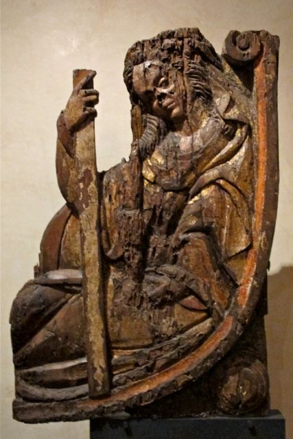 Carved wood woman sitting -- back curved into chair.