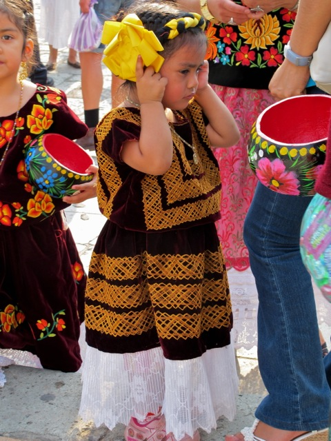 Girl in Istmo costume covering her ears