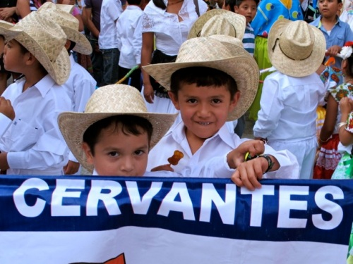 "Boys in white shirts and straw cowboy hats holding school banner reading ""Cervantes"""