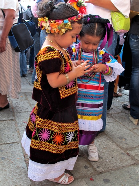 2 girls standing together; one in Istmo costume and one in Tuxtepec costume