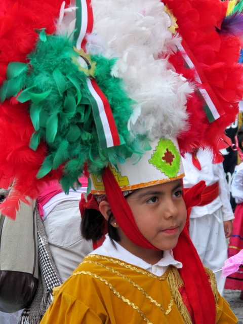 Closeup of boy with Danza de la Pluma head dress.