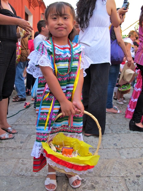 Girl in Tuxtepec costume holding basket of candy.