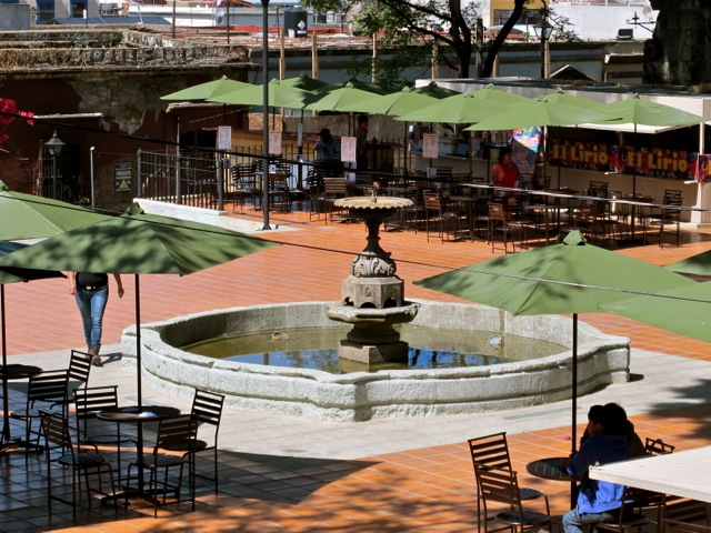 Fountain and green umbrellas on terracotta paved terrace.