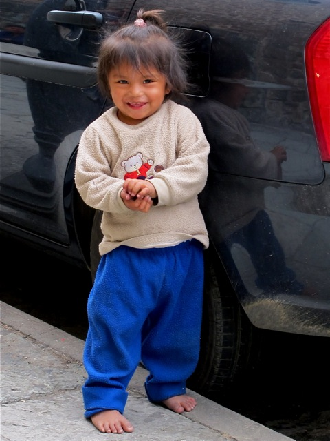 Young child, barefoot standing next to a car