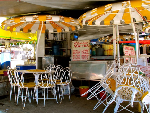 Yellow and white iron chairs and umbrellas in front of the Nevería Malena stand.