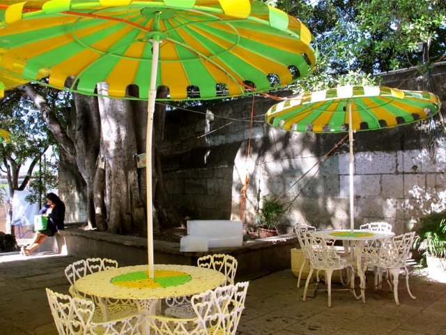 Green and yellow iron chairs and umbrellas in front of a neveria stand.