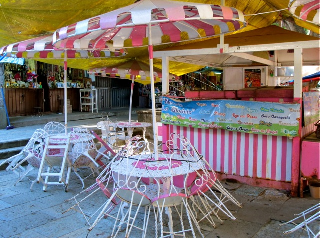 Pink and white iron chairs and umbrella in front of a neveria stand.