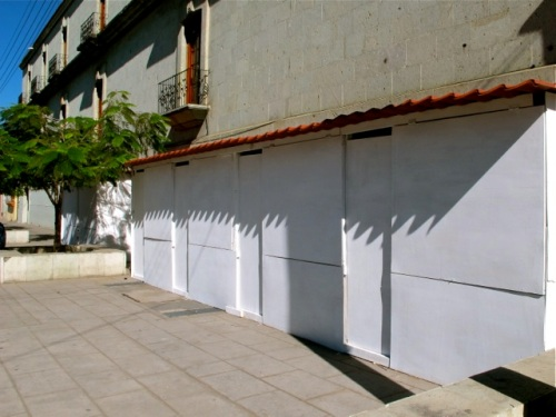 Wooden puestos lining sidewalk.