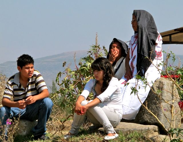 Woman with rebozo on her head, sitting on side of hill with 3 children