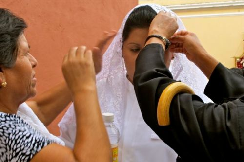 2 women pining veil on young woman