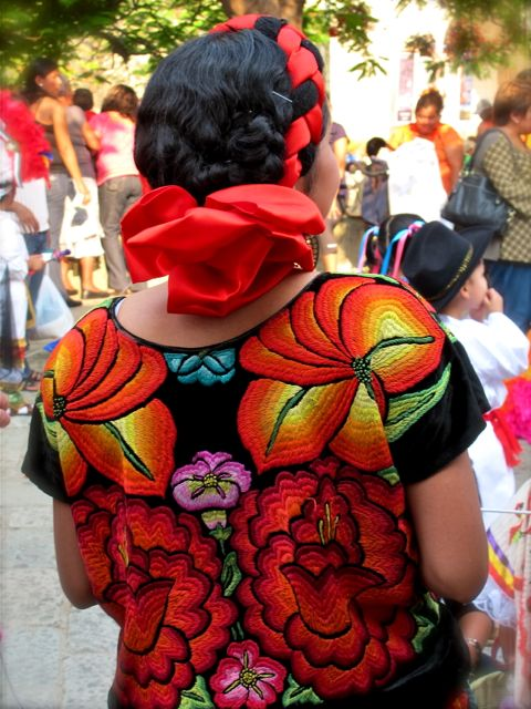 Close up of the back of a brightly embroidered huipil on black velvet