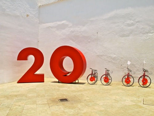 20 and 4 bicycles with a comma in the center of the front wheels