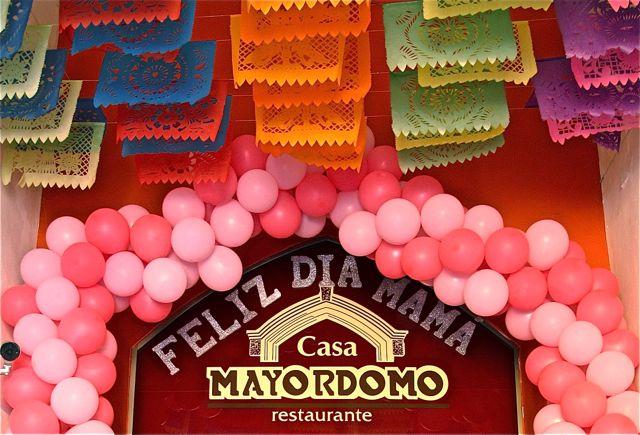 """Sign under papel picados at Casa Mayordomo Restaurante: """"Feliz dia mama"""