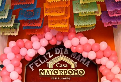 "Sign under papel picados at Casa Mayordomo Restaurante: ""Feliz dia mama"