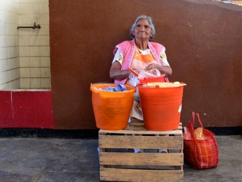 White-haired woman sitting behind two plastic buckets full of tamales
