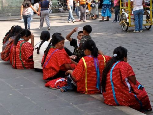 Triqui women sitting on a sidewalk