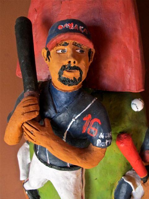 Closeup of baseball player on sculpture with bat on shoulder, wearing Guerreros de Oaxaca cap and jersey.
