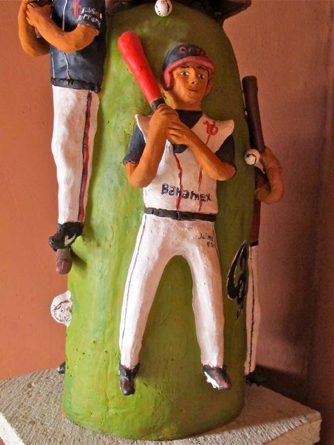 Baseball player on sculpture, with bat on shoulder.