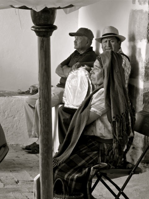 Black and white photo of Zapotec woman sitting upright with a rebozo draped on her head.