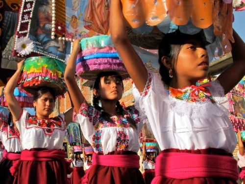 3 young women carrying canastas on their heads