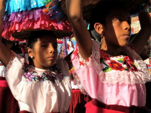 Close-up of 2 young women carrying canastas on their heads